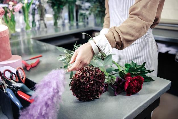 Esta listo. decorador profesional de pie en su lugar de trabajo y tomando flor