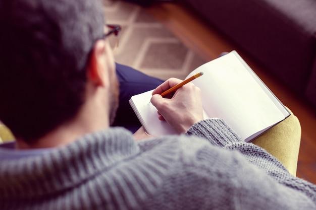 Listo para escribir. vista superior de un buen hombre inteligente sosteniendo su bolígrafo mientras está listo para escribir