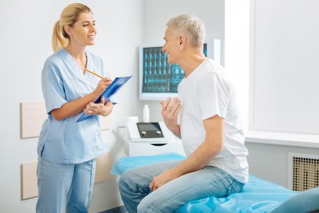 Listo para escuchar. encantado de buen doctor inteligente sonriendo y mirando a su paciente mientras está listo para escuchar sus quejas