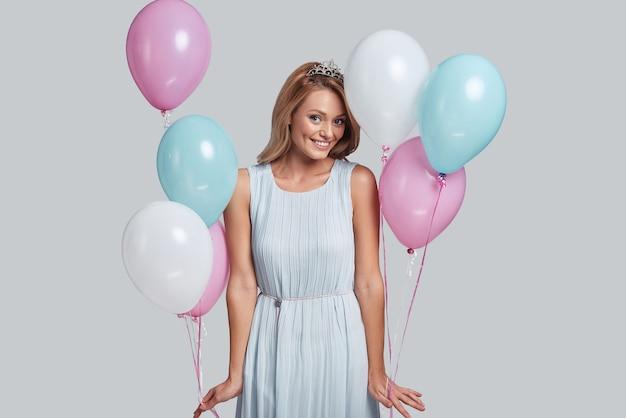 Listo para la fiesta. atractiva mujer joven sosteniendo globos y mirando a la cámara con una sonrisa mientras está de pie contra el fondo gris