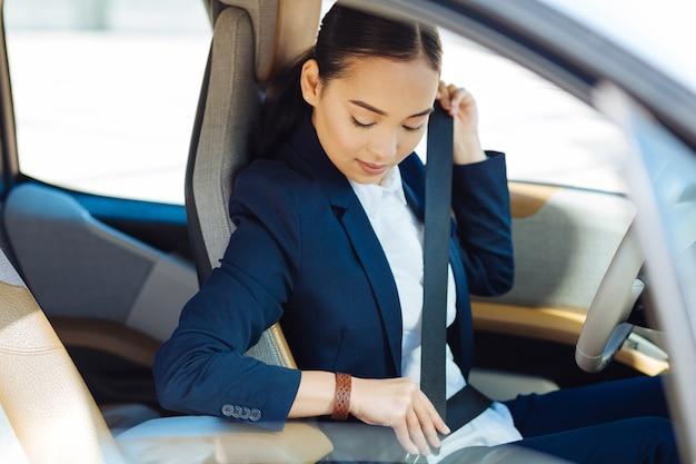 Listo para ir. bonita mujer seria mirando su cinturón de seguridad mientras está listo para ir