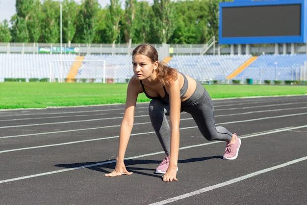 Listo para ir. ciérrese encima de la foto de la atleta de sexo femenino en la línea de salida del comienzo bajo. chica en la pista del estadio, preparándose para una carrera. concepto deportivo y saludable