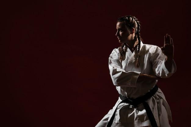 Listo para luchar contra la mujer en uniforme de karate blanco