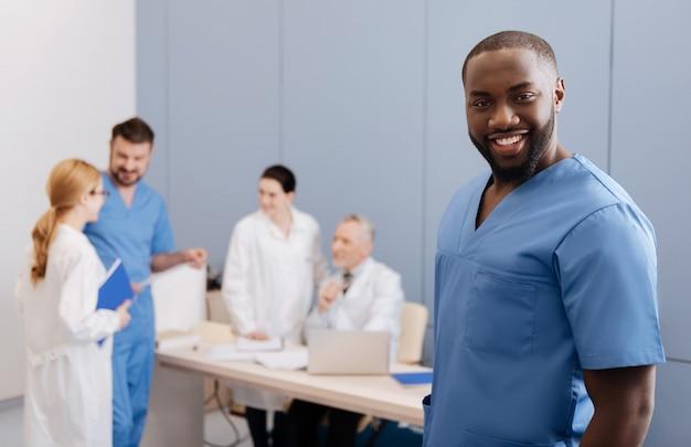 Listo para salvar vidas. carismático joven practicante afroamericano sonriendo y disfrutando de la conferencia en la clínica mientras sus colegas conversan