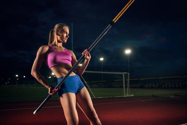 Listo para superar las dificultades. formación profesional de salto con pértiga femenino en el estadio por la noche. practicando al aire libre. concepto de deporte