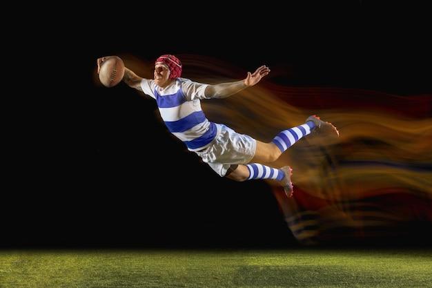 Listo para volar y ganar. un hombre caucásico jugando al rugby en el estadio con luz mixta