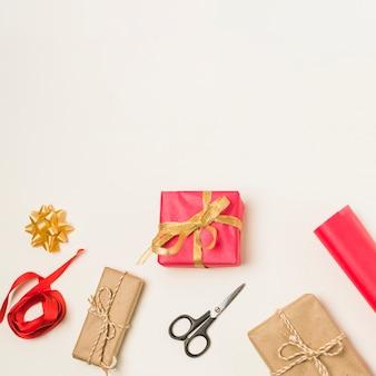 Listón rojo; arco; tijera y rollo de papel de regalo con cajas de regalo envueltas aisladas en fondo blanco