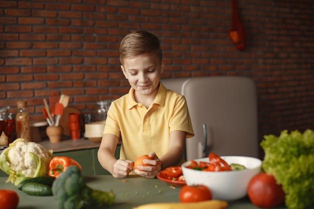 Litle boy preparar salan en una cocina