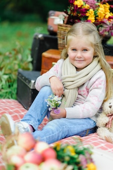 Litlle niña sentada sobre una manta en el césped