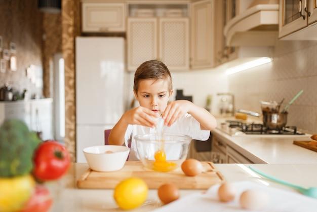 Litte boy revuelve huevos crudos en un bol, preparación de pastelería.