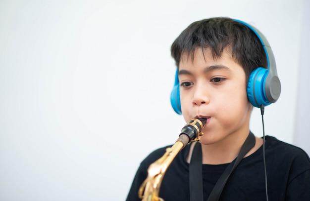 Little asian boy estudiar música de instrumentos de saxofón en línea en casa