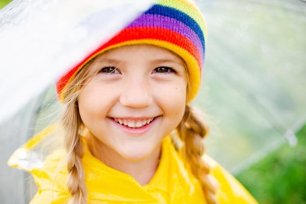 Little blonde girl smiles salta sobre charcos en primavera en un impermeable amarillo y botas de goma con paraguas
