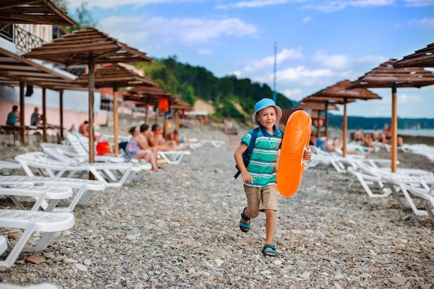 Little boy de 6 años con un sombrero con un círculo naranja inflable corre