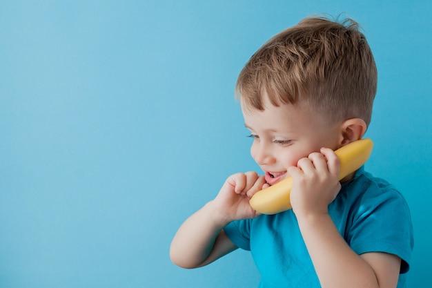 Little boy intenta hablar por medio de una banana en lugar de un teléfono.