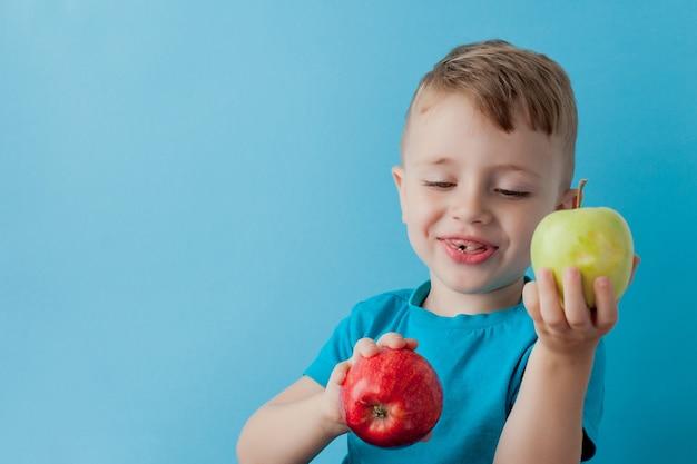 Little boy sosteniendo una manzana en sus manos sobre fondo azul, dieta y ejercicio para un buen concepto de salud