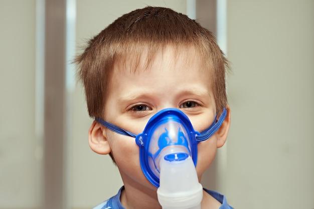 Little boyl usando un inhalador en interiores