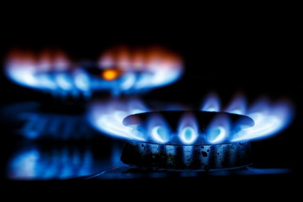 La llama azul de los dos quemadores de gas de la estufa de la cocina en la oscuridad.