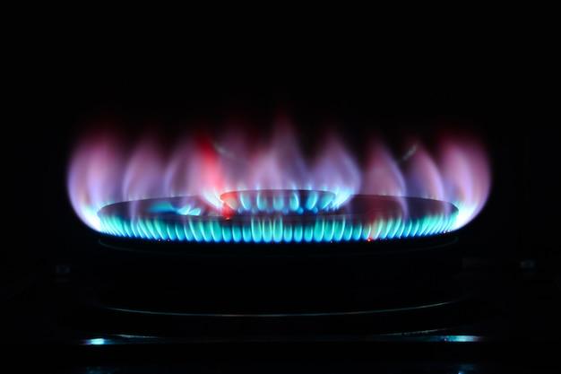 La llama azul de un quemador de cocina en la oscuridad