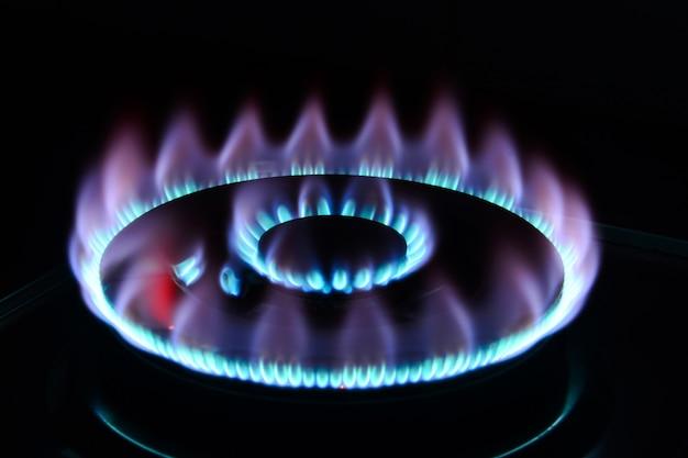 La llama azul de un quemador de cocina en la oscuridad.