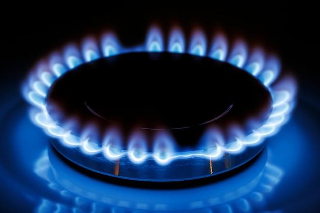 La llama azul del quemador de gas de la estufa de la cocina en la oscuridad.