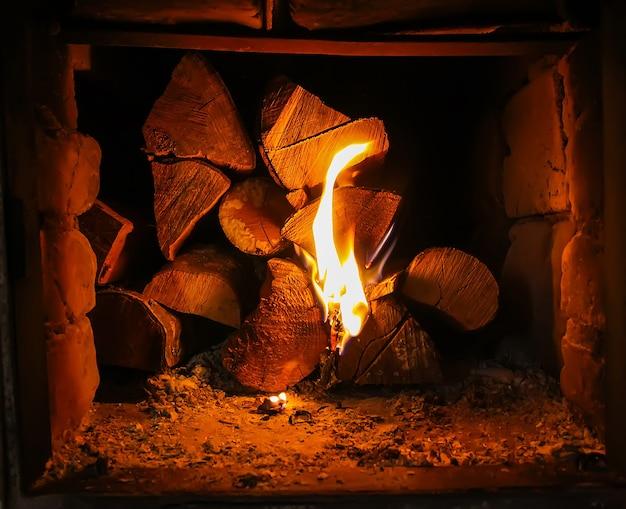 Llama caliente y leña en estufa vieja en el pueblo.