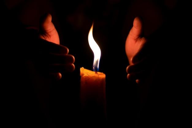 Llama de fuego ardiente a vela y dos manos protegen el viento.