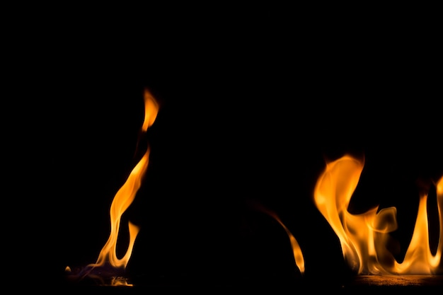 Llama de fuego sobre fondo negro. fondo texturizado llama de fuego de fuego.