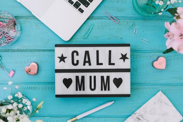 Llama a mamá inscripción con flores y portátil.