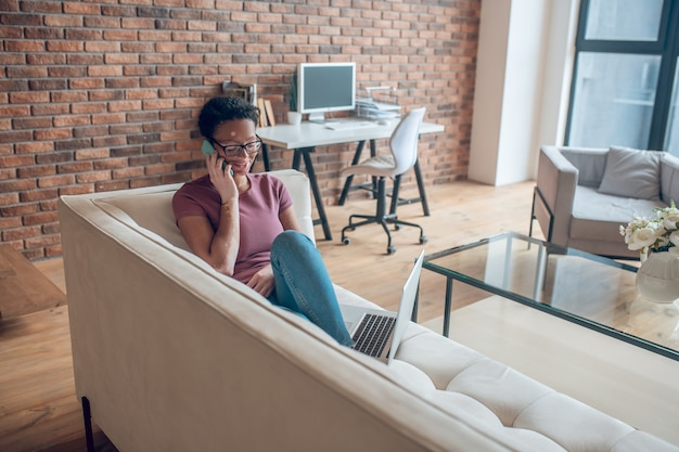En la llamada. una mujer en anteojos hablando por teléfono y mirando involucrada