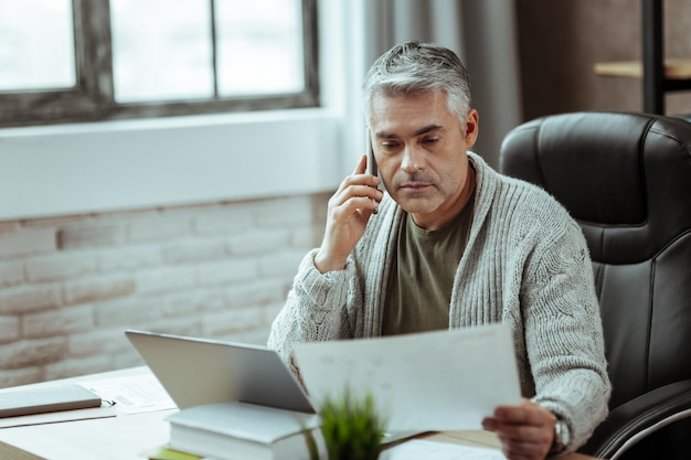 Llamada telefónica. hombre maduro inteligente haciendo una llamada mientras mira el documento