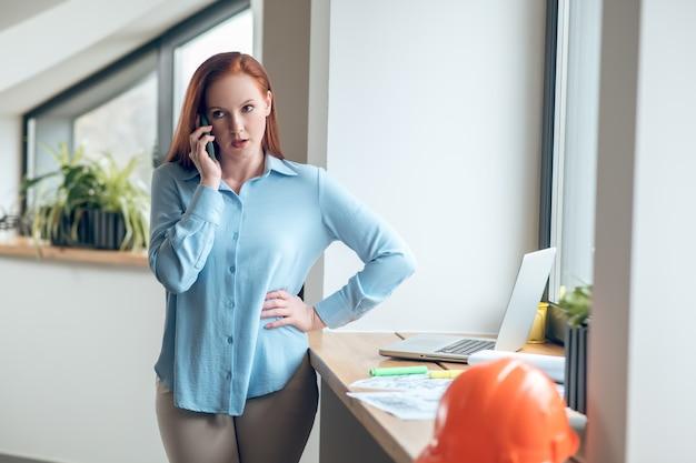 Llamada telefónica. mujer bonita joven seria hablando por teléfono inteligente cerca de la computadora portátil y casco protector en el alféizar de la ventana en el interior