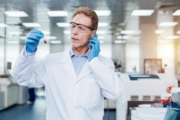 Llamada telefónica. trabajador médico seguro que mantiene el vaso de prueba en la mano derecha mientras lo examina y conversa
