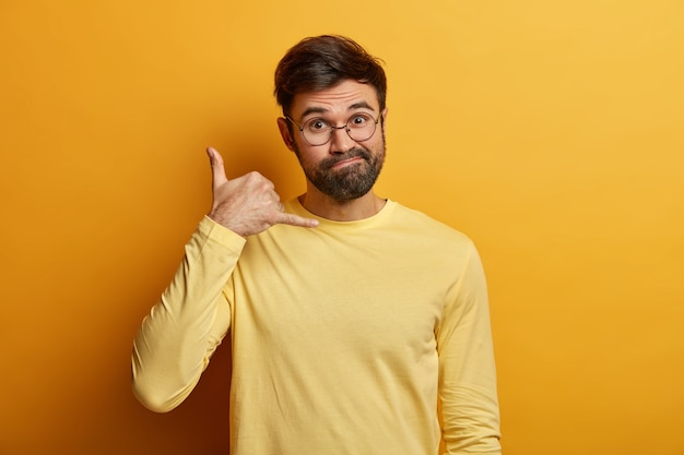 Llamame. el hombre sin afeitar desconcertado hace un gesto de llamada con los dedos, pregunta el número de teléfono, dice reunirse la próxima vez, se viste de manera informal, usa un jersey informal, aislado en una pared amarilla. lenguaje corporal