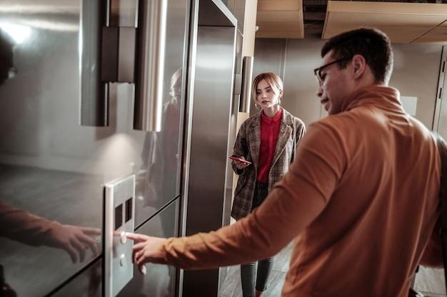 Llamando al ascensor. hombre de cabello oscuro vestido con cuello de polo naranja llamando al ascensor de pie cerca de su novia
