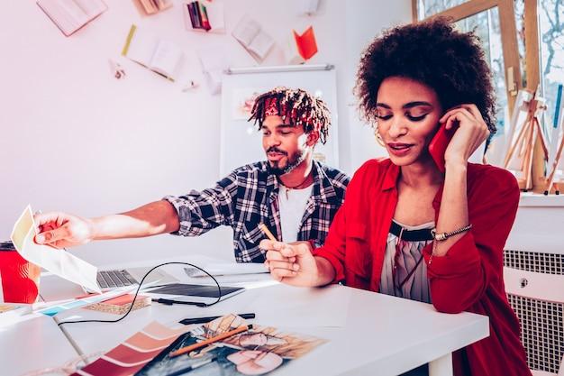 Llamando al cliente. hermosa diseñadora rizada que llama a su cliente mientras trabaja con su guapo esposo