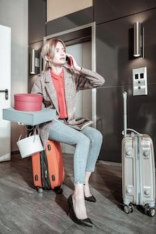 Llamando al taxi. novia rubia sosteniendo cajas llamando al taxi mientras está sentado en la maleta