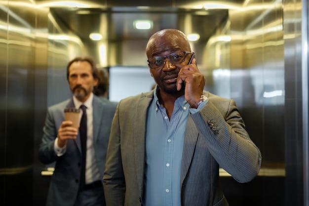 Llamando a un colega. empresario de ojos oscuros con gafas llamando a su colega mientras está de pie en el ascensor