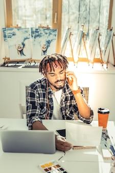 Llamando colega. joven artista sin experiencia que llama a su colega y le hace algunas preguntas.