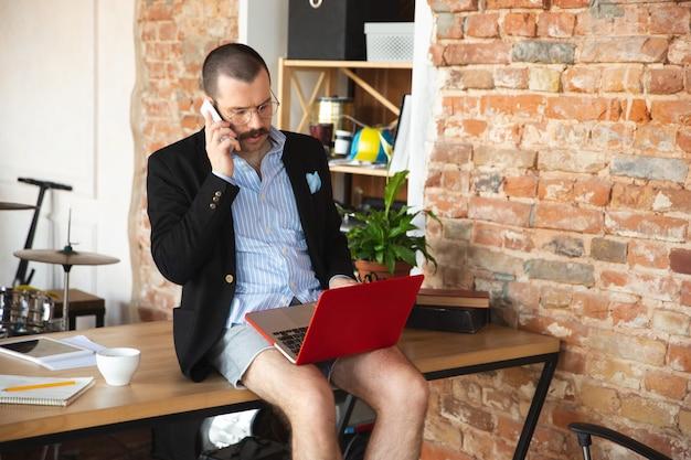 Llamando a joven sin pantalones pero con chaqueta trabajando en una computadora portátil