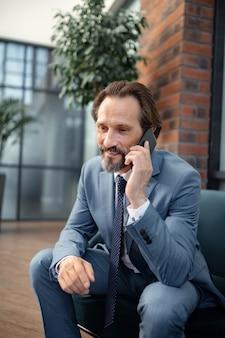 Llamando a su esposa. empresario barbudo sonriendo mientras llama a su esposa mientras trabaja en la oficina
