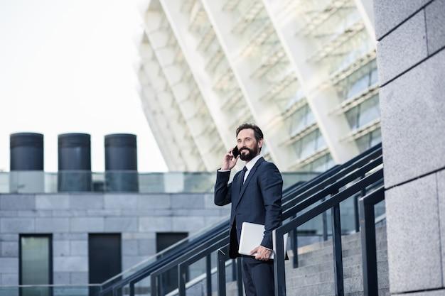 Llamar de vuelta. hombre de negocios agradable sonriente sosteniendo una computadora portátil mientras habla por teléfono