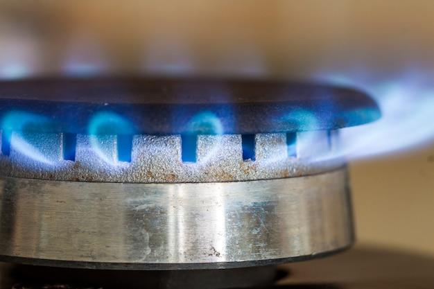 Las llamas azules de gas natural se queman en la placa de la estufa de la cocina, foto de primer plano con poca profundidad