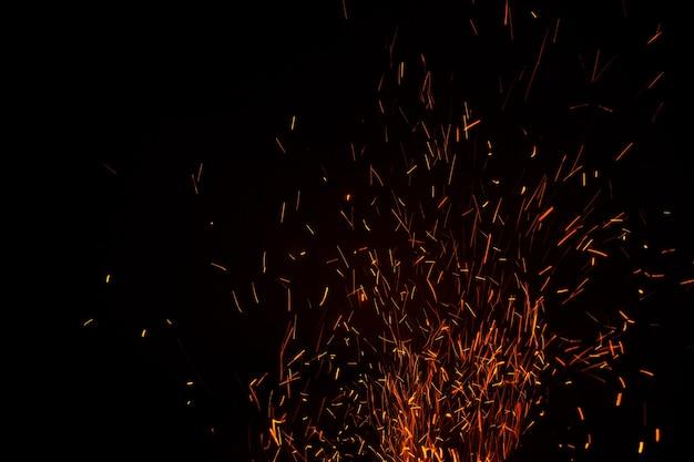 Las llamas de la oscuridad flotan en el aire. carbón de leña encendido.