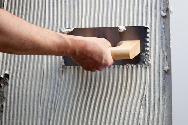 Llana dentada de construcción con cemento blanco.