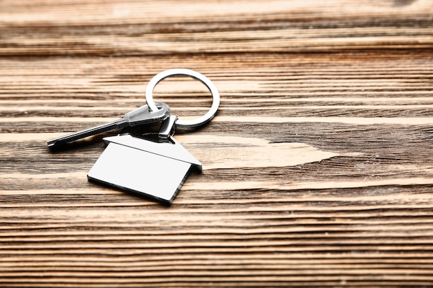 Llave con abalorio en forma de casa en madera. concepto de hipoteca