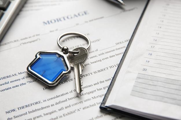 Llave con baratija en forma de casa y organizador personal en contrato hipotecario
