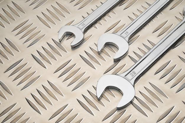 Llave de boca doble sobre placa de metal con fondo de patrón de diamante