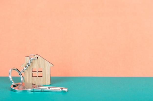 Una llave en una casa con forma de llavero de madera.