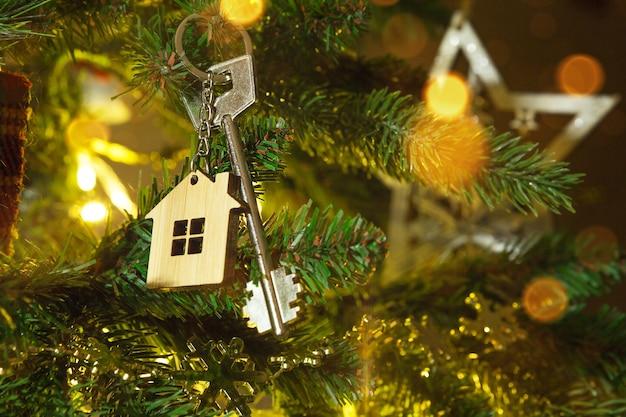La llave de la casa con un llavero cuelga del árbol de navidad. un regalo para año nuevo, navidad. construcción, diseño, proyecto, mudanza a nueva casa, hipoteca, alquiler y compra de inmuebles. copia espacio