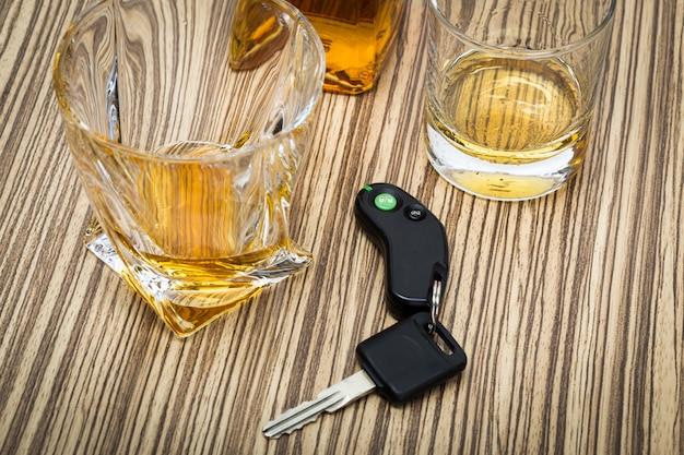 Llave del coche en la barra con alcohol derramado.